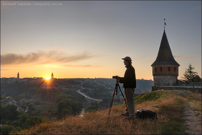 Фотограф возле крепости на рассвете